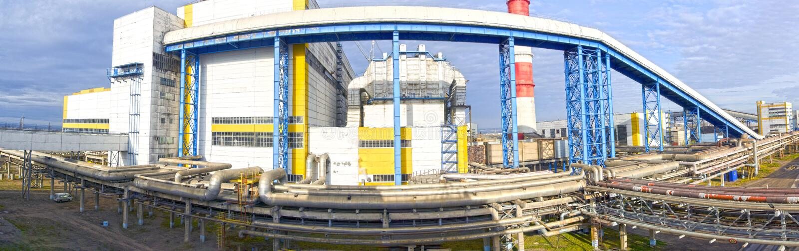 The territory of an industrial enterprise. Fuel and oil tanks. Interlacing of huge, industrial pipes in the factory. Panorama.  royalty free stock image