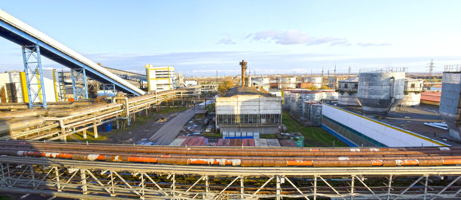 The territory of an industrial enterprise. Fuel and oil tanks. Interlacing of huge, industrial pipes in the factory. Panorama.  stock photos