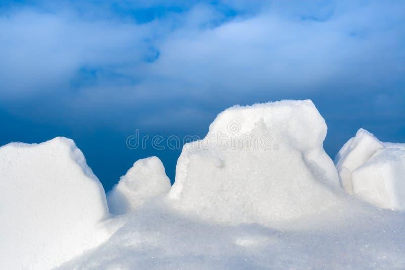 Terrones blancos de la nieve del primer contra el cielo azul fotografía de archivo