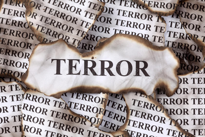 Terror. Burnt Terror. Burnt pieces of paper with the word Terror. Close-up royalty free stock images
