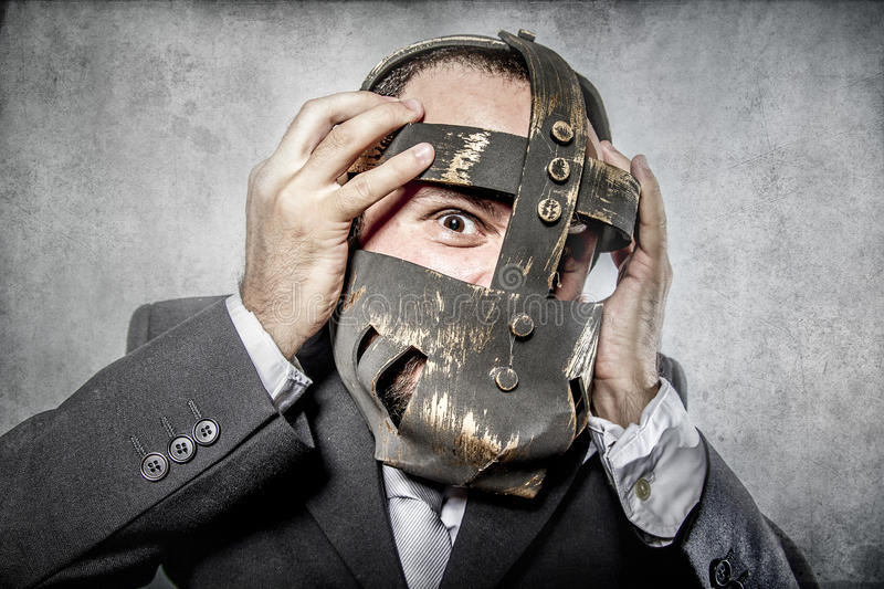 Terror, business man with iron mask. Fantasy, man beard and suit with intense expression stock photo