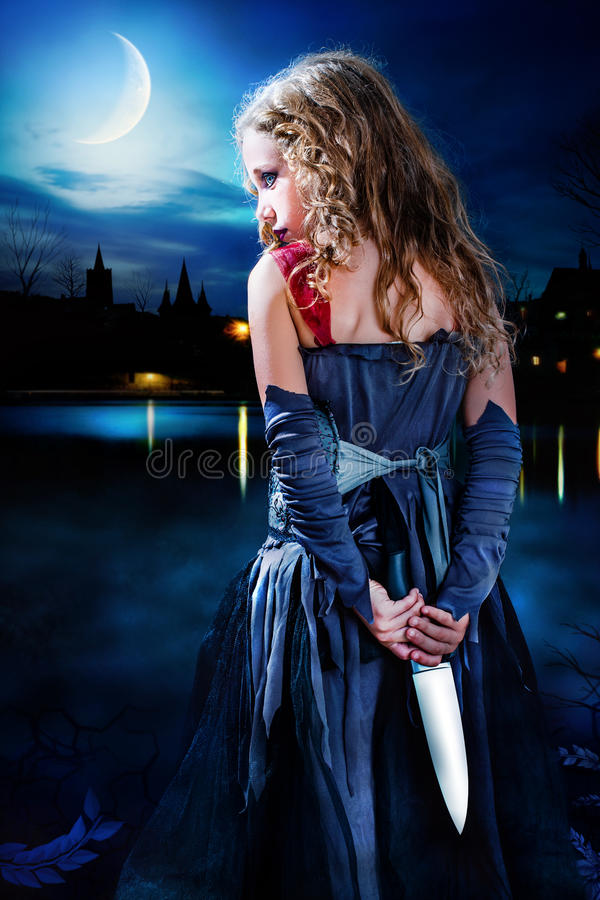 Terror girl holding knife at moonlit lake. stock photo
