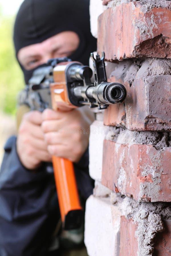 Terrorist in black mask with gun stock photography