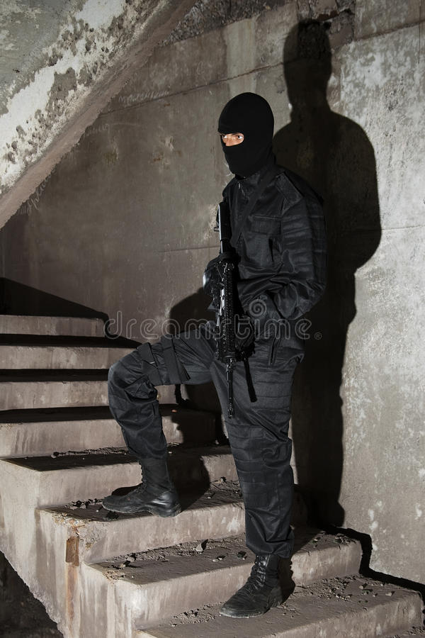 Terrorist in black mask on staircase royalty free stock photography