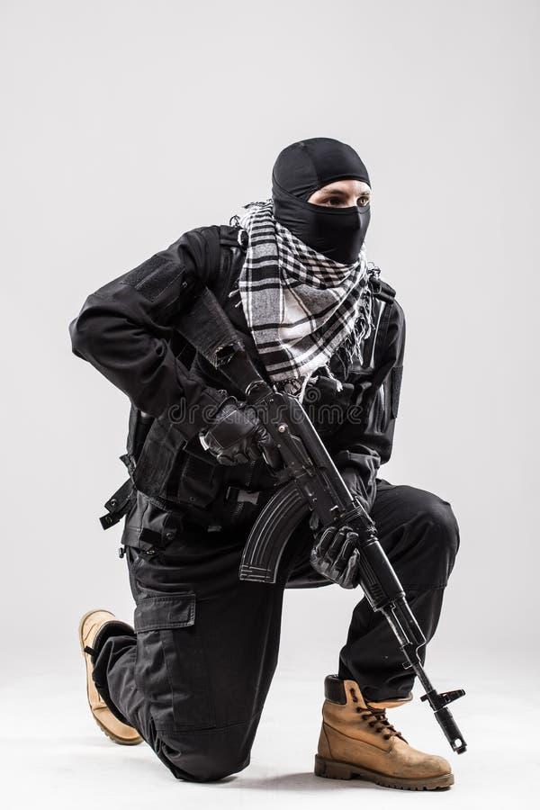 Terrorist, der ein Maschinengewehr in seinen Händen lokalisiert über Weiß hält stockbilder