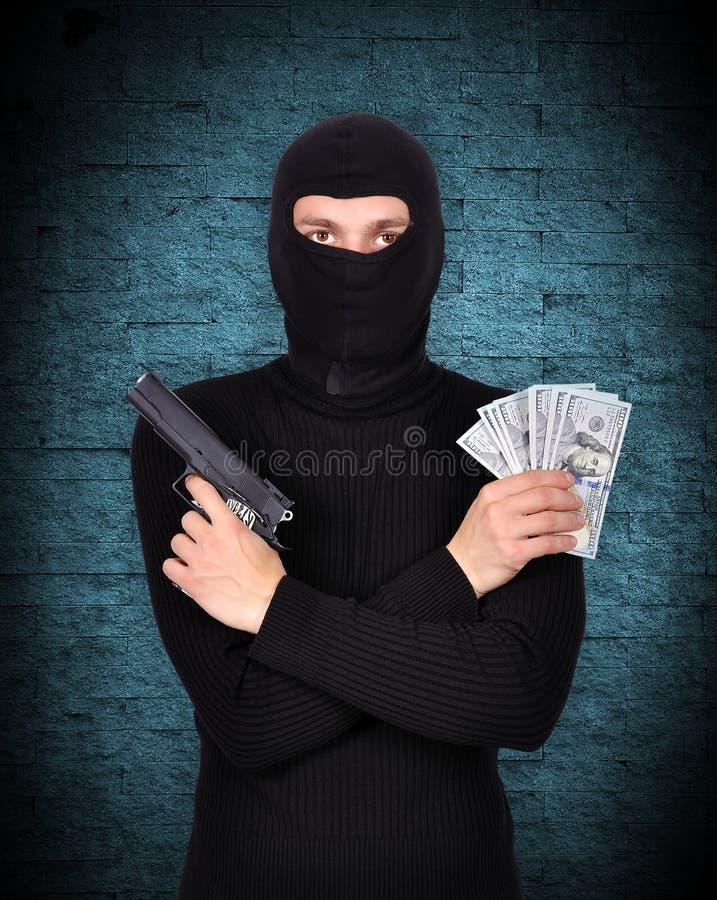 Terrorist, der Gewehr und Dollar hält lizenzfreies stockfoto