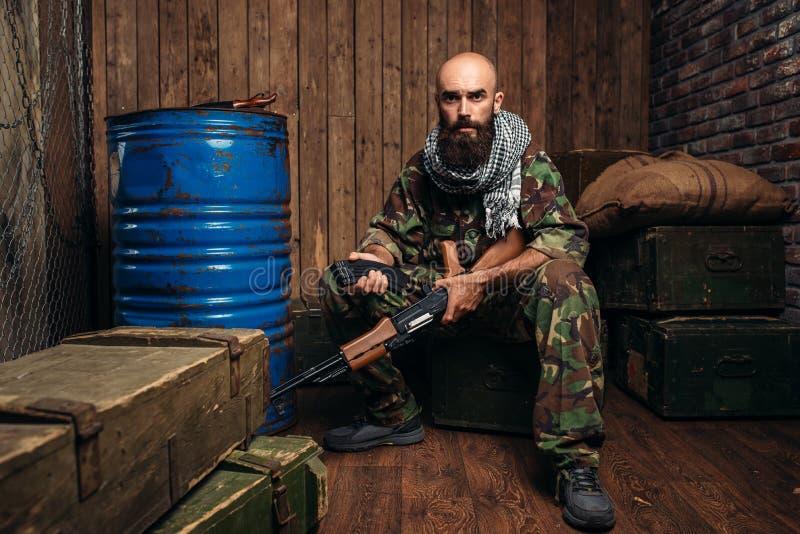 Terrorist inserts magazine into kalashnikov rifle. Terrorist in uniform inserts the magazine into the kalashnikov rifle. Terrorism and terror, soldier in royalty free stock photos