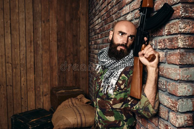 Terrorist with rifle hiding behind a wall. Terrorist in uniform with kalashnikov rifle hiding behind a wall, male mojahed with weapon. Terrorism and terror stock photography