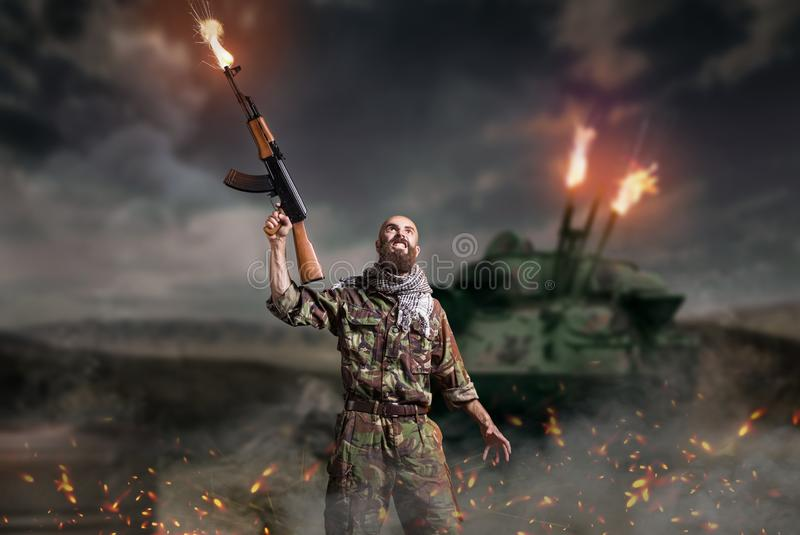 Terrorist with rifle stands in explosion and fire. Bearded terrorist with rifle in hands stands in explosion and fire. Terrorism and terror, soldier in khaki royalty free stock photos