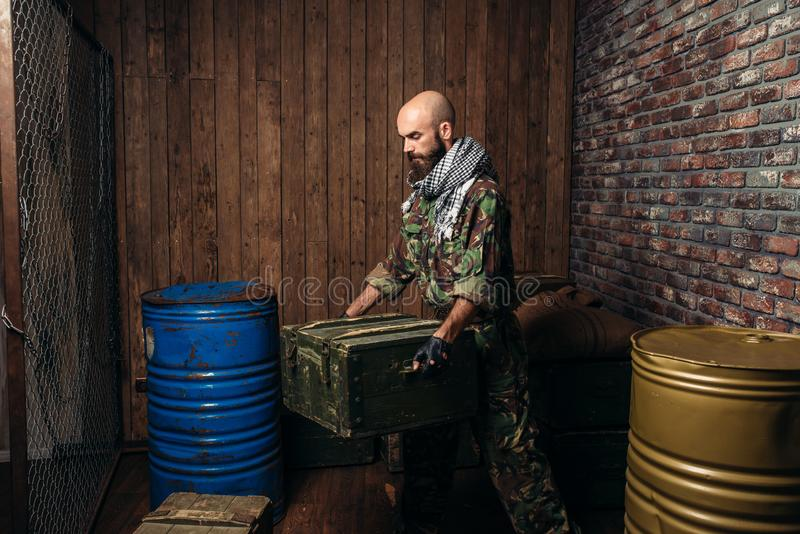 Terrorist in uniform loads boxes of ammunition. Terrorism and terror, soldier in camouflage replenish the arsenal, barrels of fuel or chemicals on background stock photos