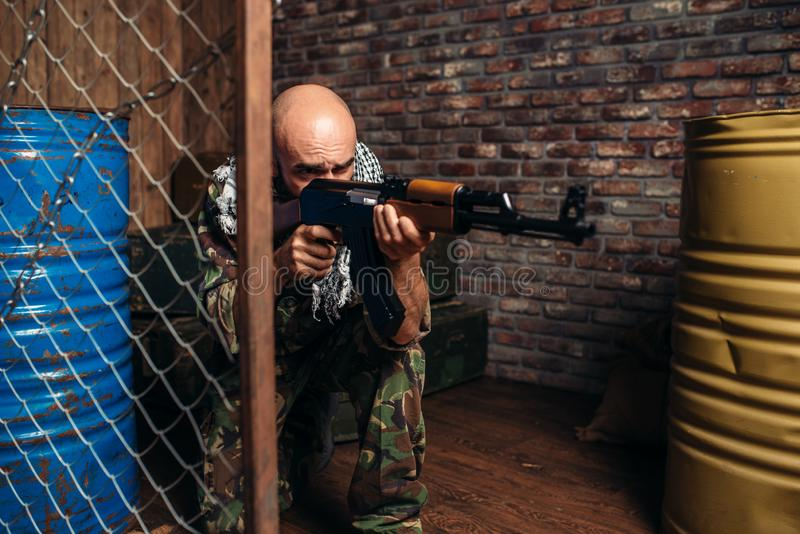 Terrorist in uniform shoots from kalashnikov rifle. Terrorist in uniform shoots from a kalashnikov rifle, male mojahed with weapon. Terrorism and terror, soldier stock photography
