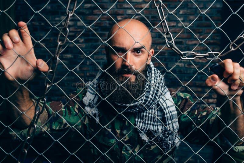 Terrorista barbuto in uniforme contro la griglia del metallo fotografie stock libere da diritti