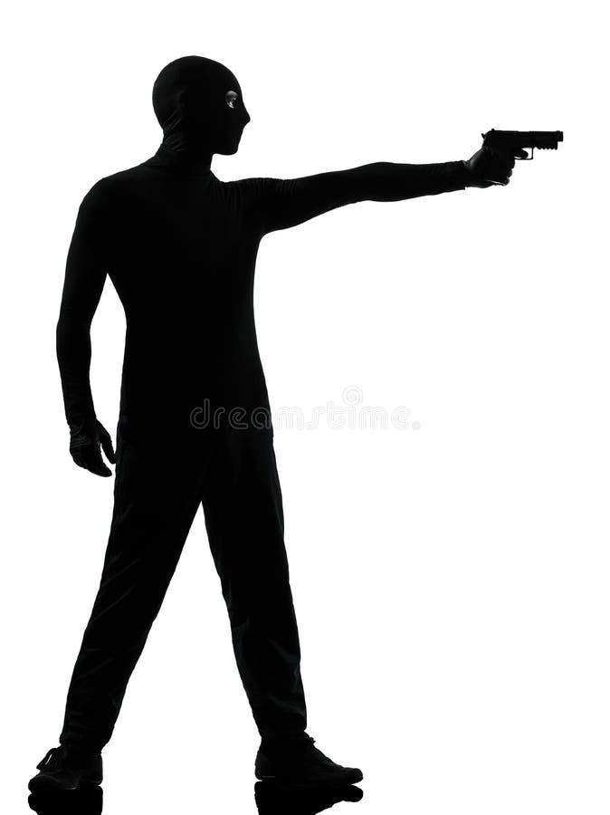 Terrorista criminal del ladrón que apunta al hombre del arma foto de archivo