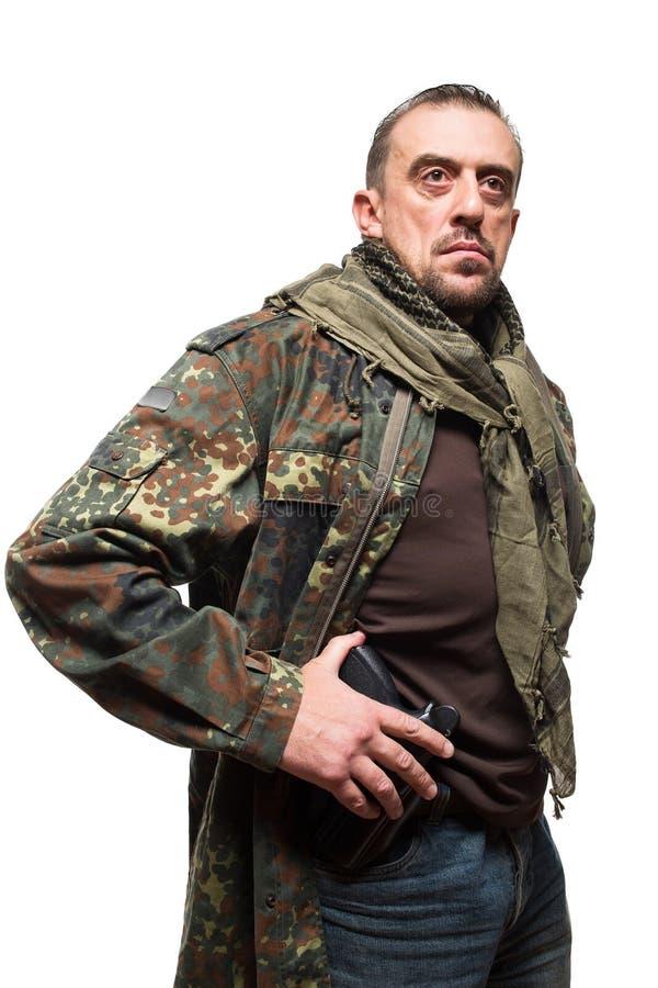 Terrorista maschio in un rivestimento militare con una pistola dentro immagini stock