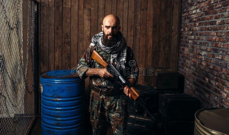 Terroristen i enhetligt rymmer kalashnikovgeväret arkivfoto