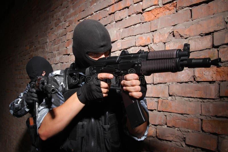Terroristes dans les masques noirs avec des canons photo libre de droits