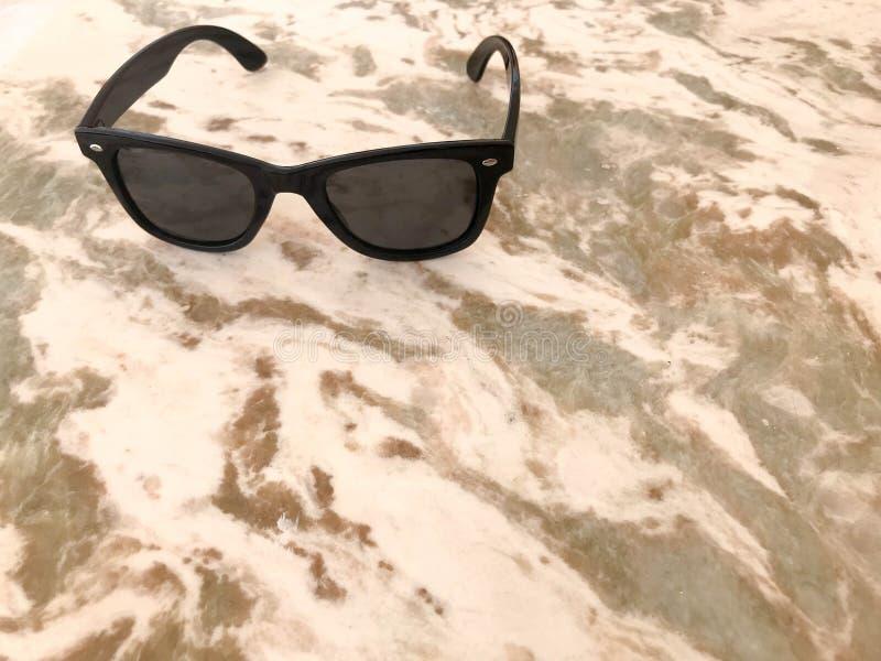 Terry-sonnenbackenplastikgläser mit schwarzem Glas und Bögen liegen auf einem sauberen braunen Sand-farbigen hellen Stein mit meh stockbilder