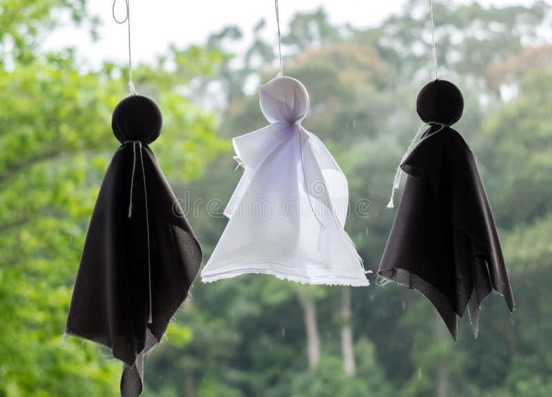 Teru Teru Bozu o lluvia japonesa hecha a mano de la muñeca en la ejecución blanco y negro del color en el techo con gota de lluvi imagen de archivo