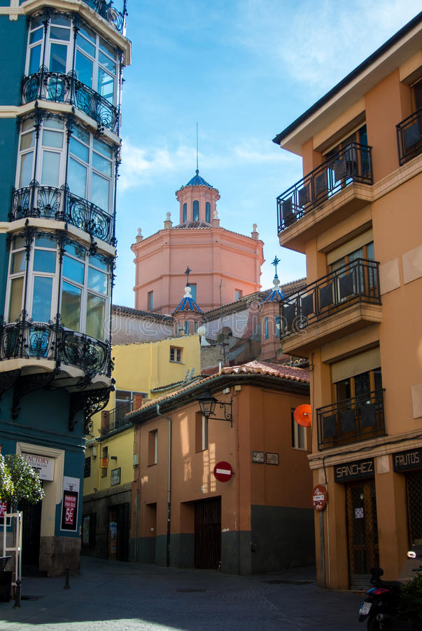 TERUEL, SPAIN - FEBRUARY 01, 2016: A narrow street with old houses in different styles and a cathedral at the background at mediev. Al town Teruel at Aragon royalty free stock images