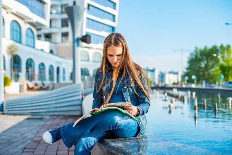 Terug naar de tiener van de schoolstudent leest het meisje een handboek Openluchtportret van jong tiener donkerbruin meisje met l stock afbeeldingen