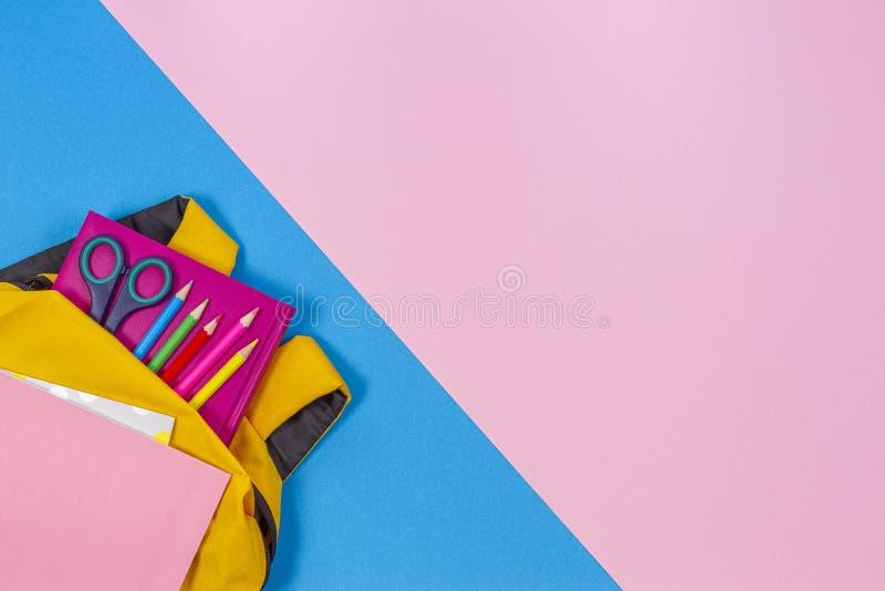 Terug naar het Concept van de School Gele rugzak met schoollevering op pastelkleur roze en lichtblauwe achtergrond Hoogste mening stock afbeelding