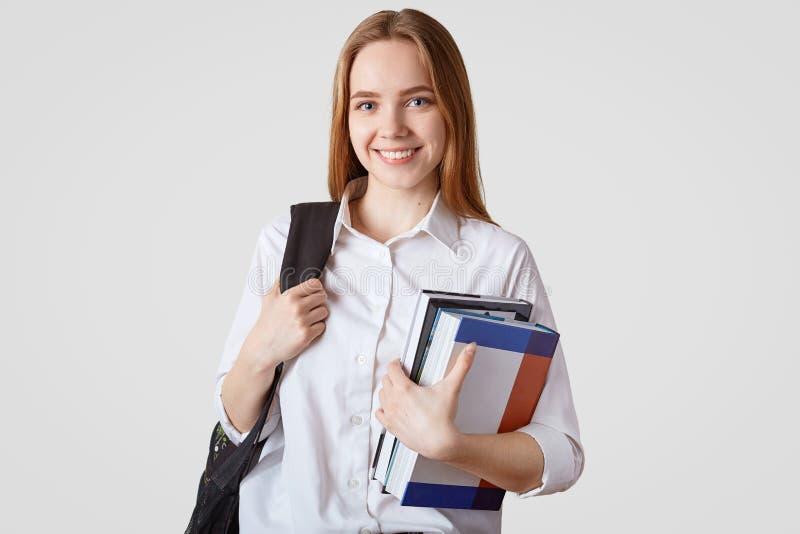 Terug naar het Concept van de School Glimlachend Europees schoolmeisje in elegante kleren, draagt rugzak en stapel van boeken, bl stock afbeeldingen