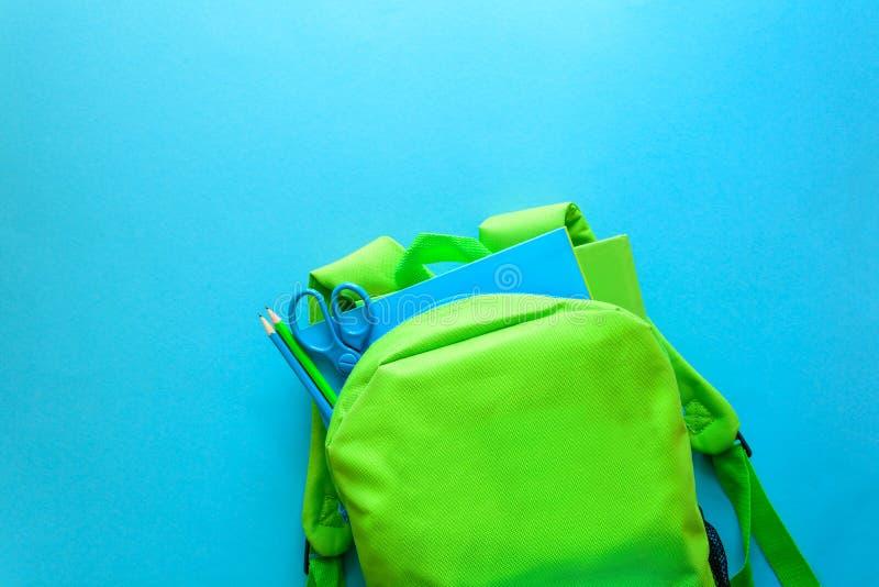Terug naar het Concept van de School Groene rugzak met schoollevering op blauwe achtergrond Hoogste mening De ruimte van het exem stock foto