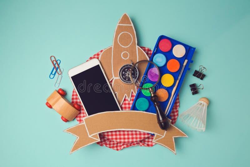 Terug naar het ontwerp van het schoolkenteken met smartphone en kartonraket Creatief de kopbalbeeld van de ontwerpheld Mening van stock fotografie