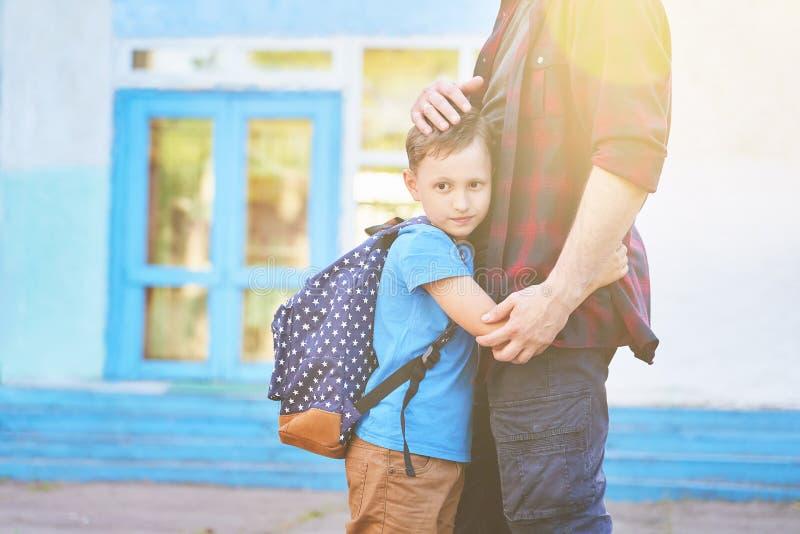 Terug naar School De gelukkige vader en de zoon omhelzen voor de basisschool De ouder neemt het kind aan lage school stock fotografie
