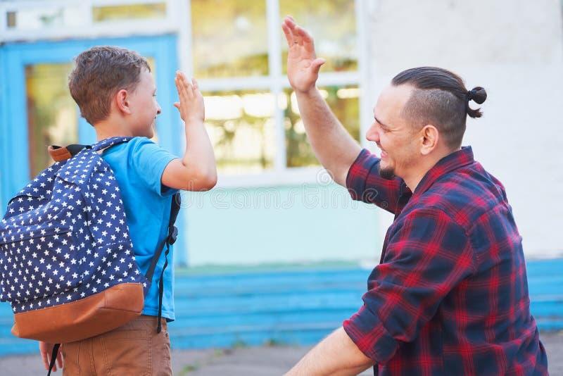 Terug naar School De gelukkige vader en de zoon zijn welkom voor basisschool de ouder ontmoet een kind van basisschool De student stock afbeelding