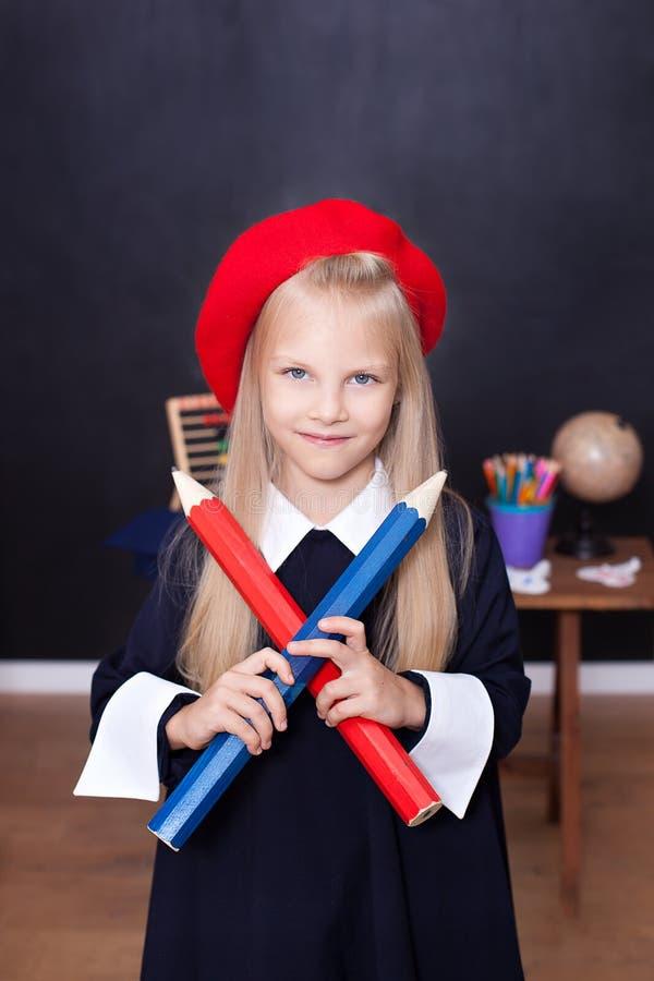 Terug naar school! Een klein meisje bevindt zich met grote potloden in haar handen op school Het schoolmeisje antwoordt aan de le royalty-vrije stock foto's