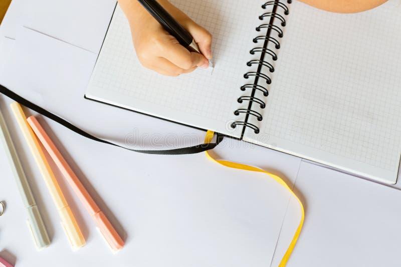 Terug naar school en gelukkige tijd De kinderen overhandigen holding pen en het schrijven in notitieboekje Jong geitje die thuisw stock afbeelding