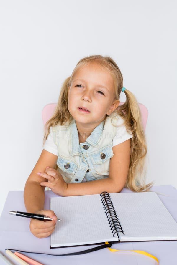 Terug naar school en gelukkige tijd Kinderen die pen houden en in notitieboekje op witte achtergrond schrijven Jong geitje die th stock afbeelding