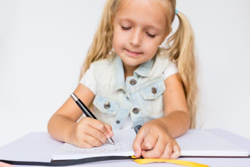 Terug naar school en gelukkige tijd Kinderen die pen houden en in notitieboekje op witte achtergrond schrijven Jong geitje die th stock foto's