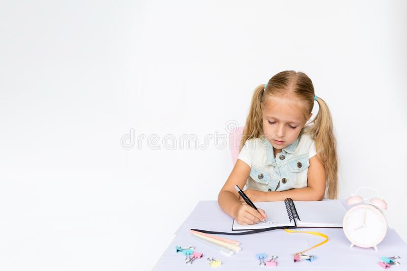 Terug naar school en gelukkige tijd Kinderen die pen houden en in notitieboekje op witte achtergrond schrijven Jong geitje die th royalty-vrije stock fotografie
