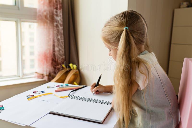 Terug naar school en gelukkige tijd Kinderen die pen houden en in notitieboekje schrijven Jong geitje die thuiswerk maken Het con royalty-vrije stock afbeeldingen