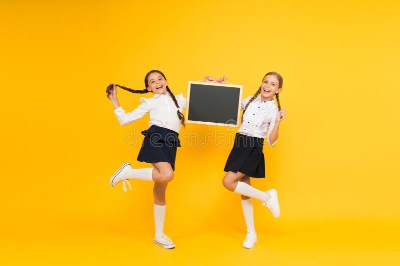 Terug naar School Gelukkige kinderen die schoolbord op gele achtergrond houden Meisjes die voor schoolles voorbereidingen treffen stock foto's