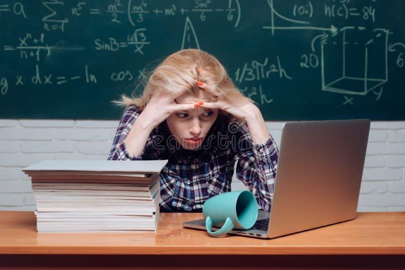 Terug naar School Het meisje beklemtoonde door te bestuderen aan harde het gillen klaslokaalachtergrond Het bestuderen bij univer stock foto's