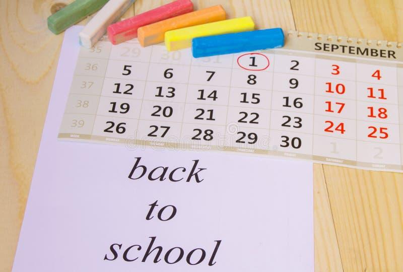 Terug naar school, kalender, kleurkrijtje op houten achtergrond stock afbeelding