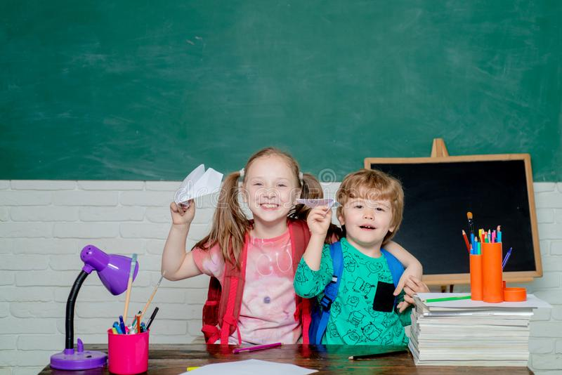 Terug naar School Leuk weinig peuterjong geitjejongen met Weinig spel van het kindmeisje met document vliegtuig in een klaslokaal royalty-vrije stock foto's