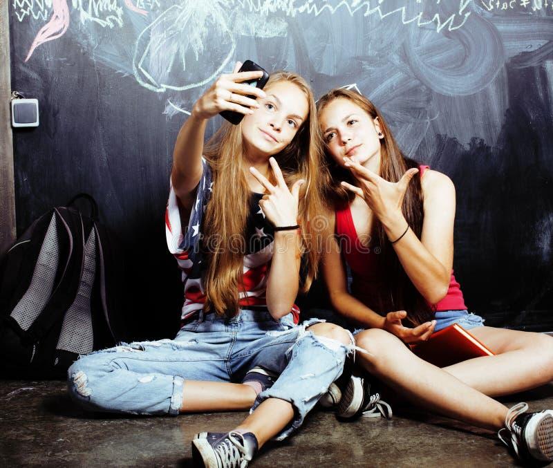 Terug naar school na de zomervakanties, twee tiener echte meisjes in klaslokaal met samen geschilderd bord, levensstijl stock afbeeldingen