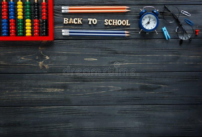 Terug naar school, onderwijsconcept Reeks van kantoorbehoeften op de grijze houten achtergrond scores, ronde glazen, potloden stock afbeeldingen