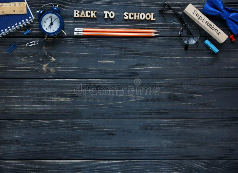 Terug naar school, onderwijsconcept Reeks van kantoorbehoeften op de grijze houten achtergrond scores, ronde glazen, potloden stock foto