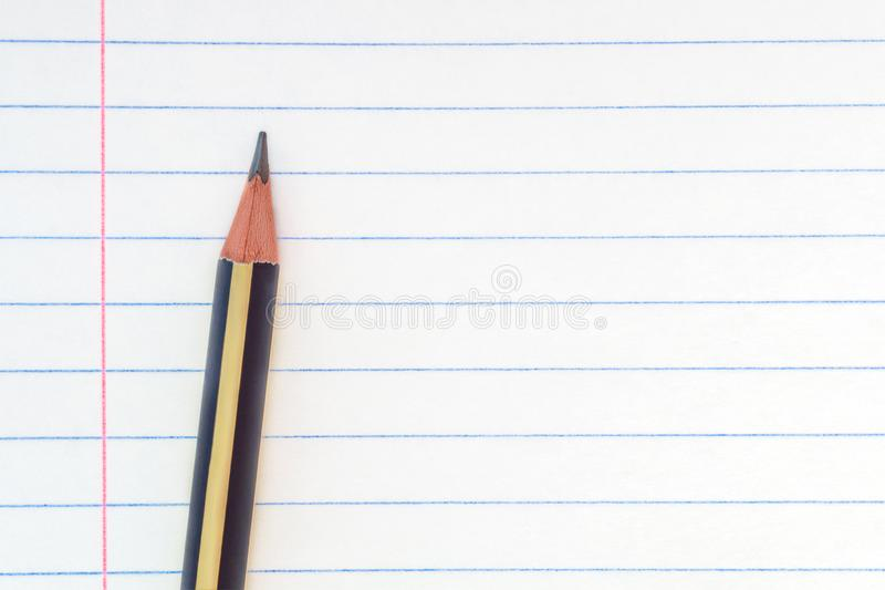 Terug naar school, onderwijsconcept - voerde het close-up gestreepte potlood op notitieboekje document achtergrond voor onderwijs royalty-vrije stock fotografie