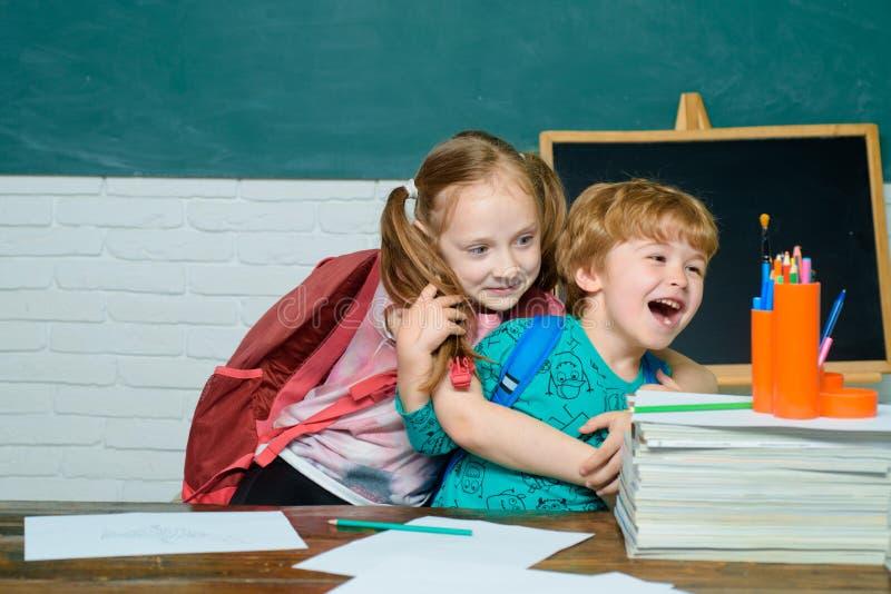 Terug naar school - onderwijsconcept Vrolijk glimlachend kind bij het bord Kind van basisschool met boek en royalty-vrije stock fotografie