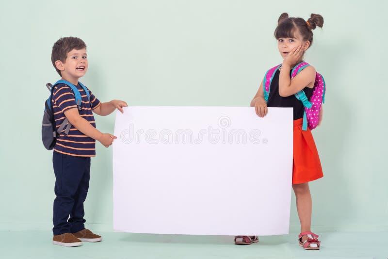 Terug naar school - reclame Schooljonge geitjes met rugzakken die witte lege of witte kaart houden royalty-vrije stock fotografie