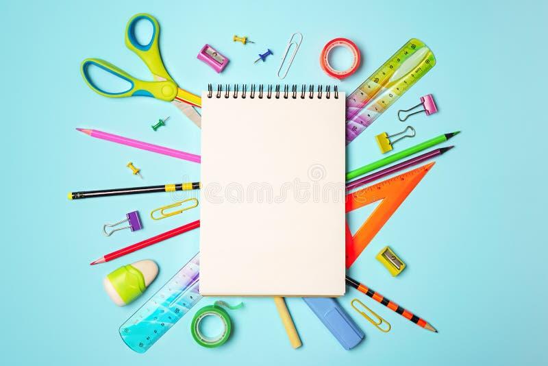 Terug naar schoolachtergrond met blocnote, kleurrijke potloden, vierkante heerser, schaar, klemmen op pastelkleur blauwe achtergr stock foto's