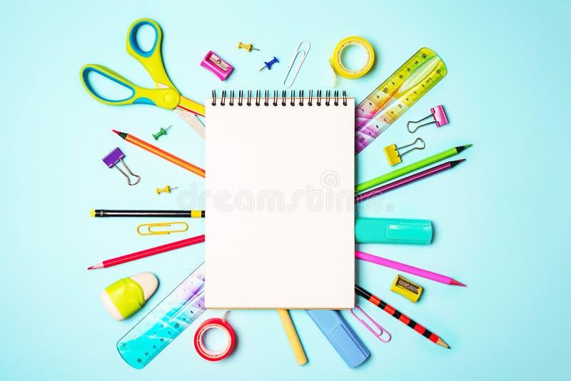 Terug naar schoolachtergrond met blocnote, kleurrijke potloden, vierkante heerser, schaar, klemmen op pastelkleur blauwe achtergr stock afbeelding