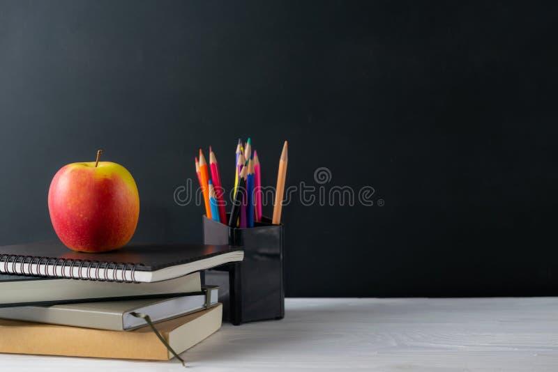 Terug naar schoolachtergrond met boeken en appel op bord stock foto's