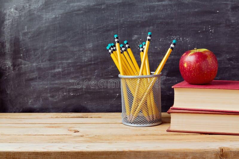 Terug naar schoolachtergrond met boeken, potloden en appel over bord royalty-vrije stock foto's